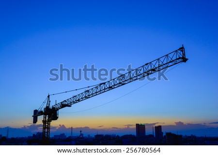 Industrial construction cranes and building in the sunset - stock photo