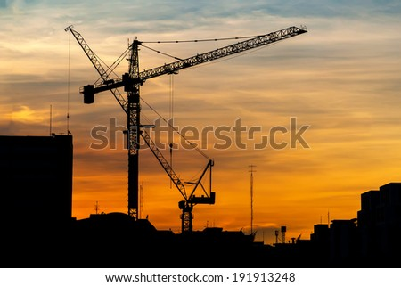 Industrial construction cranes and building silhouettes at sunset - stock photo