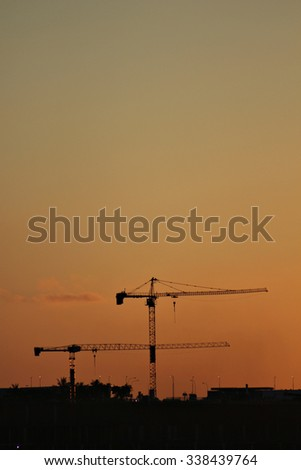 Industrial construction cranes and building silhouettes over sun at sunrise. - stock photo