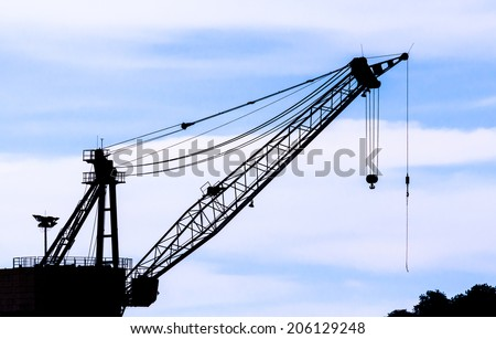 Industrial construction cranes and building silhouettes over sun at sunset  - stock photo