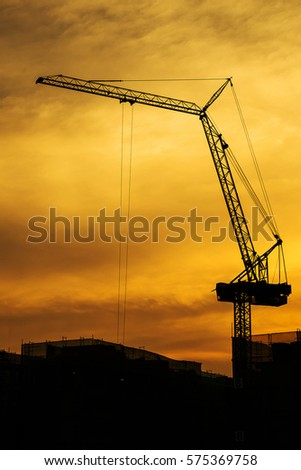 Industrial construction cranes and building silhouettes over sunset