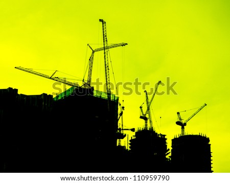 Industrial construction cranes and building silhouettes over yellow sky - stock photo