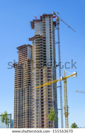 Industrial construction cranes working on building a skyscraper - stock photo