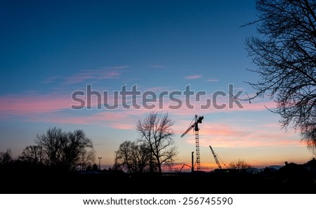 Industrial construction site at sunset with silhouette of a crane. - stock photo