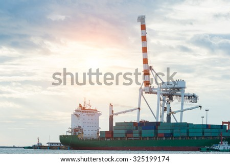 Industrial Container Cargo freight ship with working crane bridge - stock photo