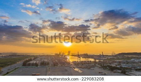 Industrial Container Cargo freight ship with working crane bridge in shipyard at dusk for Logistic Import Export background - stock photo