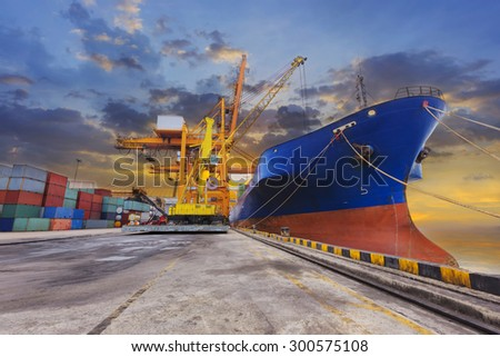 Industrial Container Cargo freight ship with working crane bridge in shipyard at dusk for Logistic Import Export at sunset - stock photo