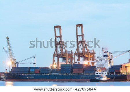 Industrial Container cargo ship with working crane bridge in the evening for a background of logistics, import and export.