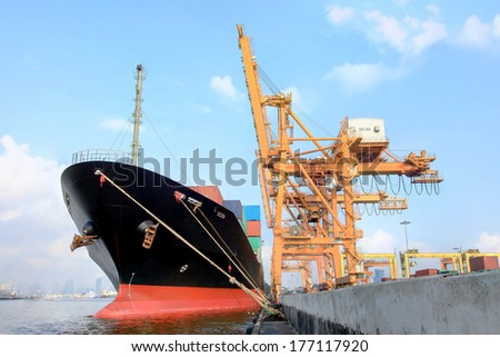 Industrial crain loading container on cargo shipfreight ship with working crane bridge in shipyard at dusk for Logistic Import Export under blue sky and cloud background