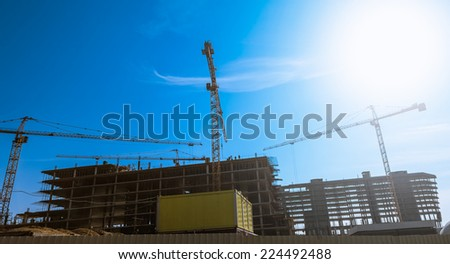 Industrial crane and building construction site against the sun and blue sky
