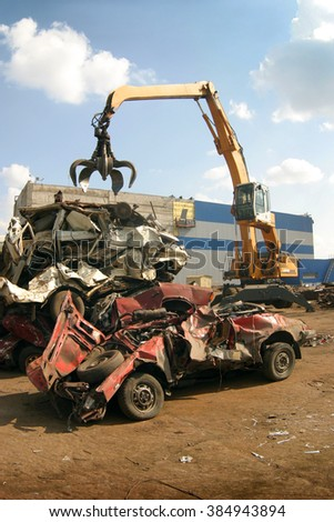 Industrial crane claw grabbing old car for recycling metal