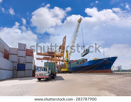 Industrial crane loading Containers in a Cargo freight ship with truck forwarders to container yard at harbor - stock photo