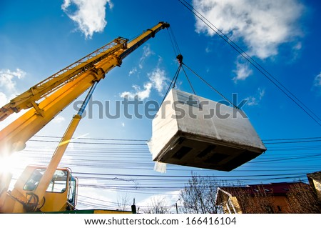 Industrial Crane operating and lifting an electric generator against sunlight and blue sky - stock photo