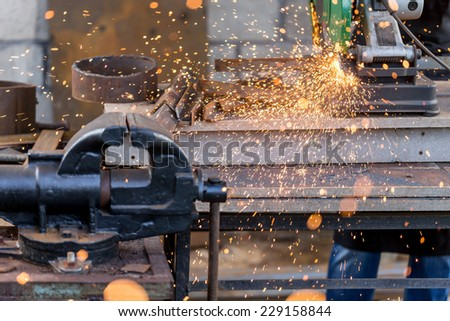 Industrial cutting metal with many sharp sparks on compound mitre saw with circular blade   - stock photo