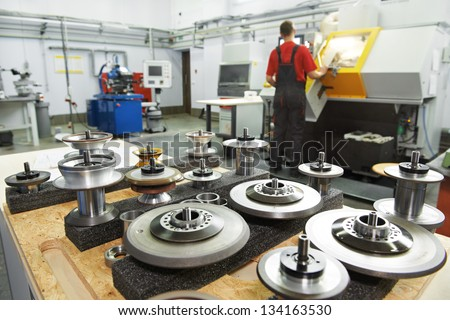 industrial cutting tools in front of cnc milling machine center in tool workshop manufacturing - stock photo