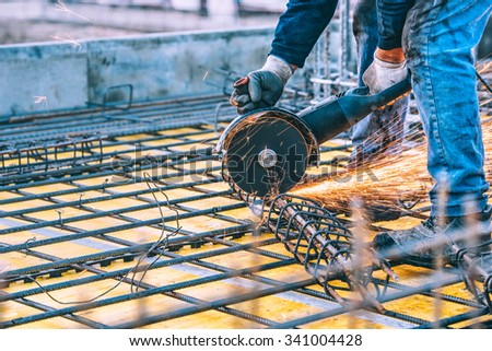 industrial details with worker cutting steel bars and reinforced steel with angle grinder. Filtered image - stock photo
