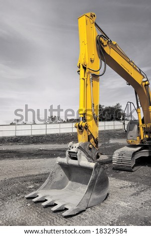 Industrial digger with bucket, standing idle on hardcore. Desaturated with only the yellow of the digger in color. - stock photo