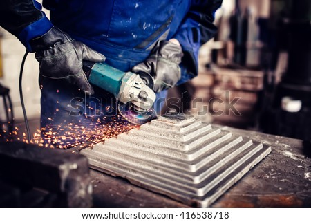 industrial engineer working on cutting a metal and steel bar with angle grinder, metallurgic factory details - stock photo