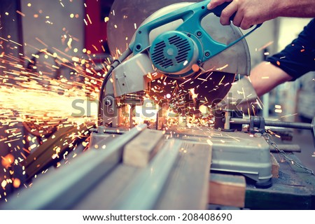 industrial engineer working on cutting a metal and steel with compound mitre saw with sharp, circular blade - stock photo