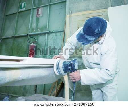 Industrial environment. Worker planing wood board with electrical equipment.
