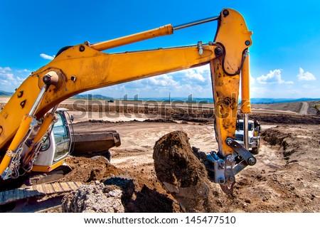 Industrial excavator bulldozer digging in sandpit and loading soil into dumper truck - stock photo