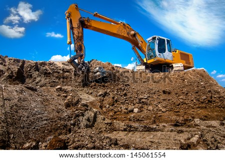 industrial excavator bulldozer in sandpit with raised bucket for