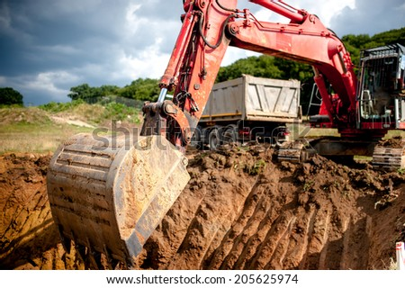 industrial excavator digging a hole and loading earth in a dumper truck at a quarry or a construction site - stock photo
