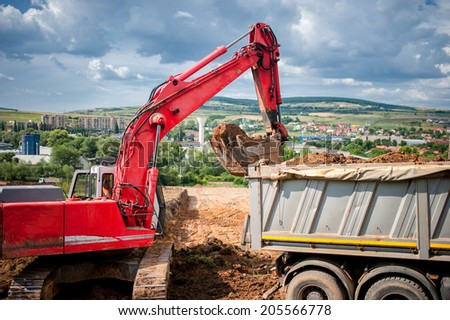industrial excavator loader with raised backhoe standing in sandpit and digging in pit  - stock photo