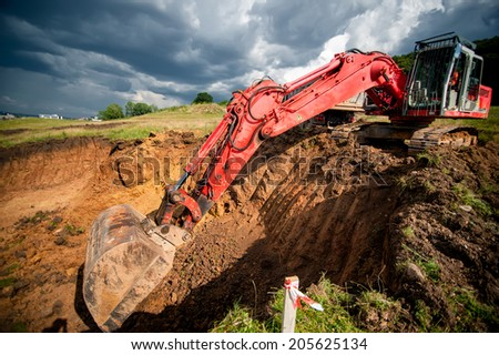 industrial excavator loading soil from highway construction site - stock photo