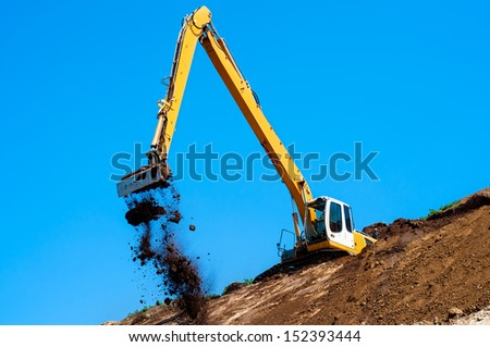 Industrial excavator loading soil material from highway construction site against blue, clear sky - stock photo