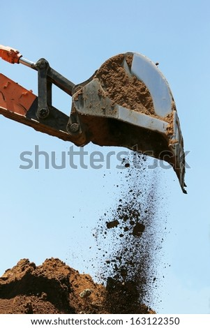 Industrial excavator machine scooping up sand and rocks - stock photo