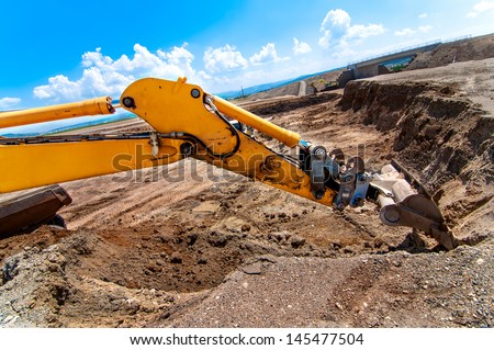 Industrial excavator moving earth and loading a dumper truck on road construction site