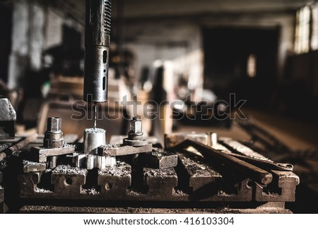 Industrial factory working details with automated lathe drilling and cutting metal  - stock photo