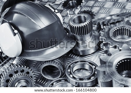 industrial hardhat set against gears, cogs and ball-bearings - stock photo
