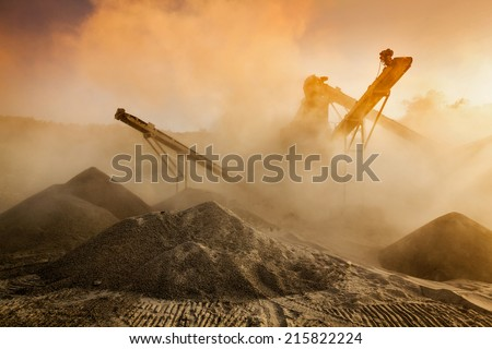 Industrial hell pollution background concept - crusher (rock stone crushing machine) at open pit mining and processing plant for crushed stone, sand and gravel on sunset - stock photo