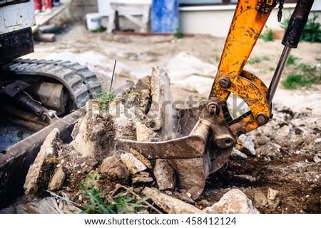 industrial hydraulic backhoe bulldozer loading concrete blocks - stock photo