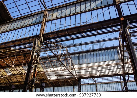 Industrial interior of an old factory building with blue sky