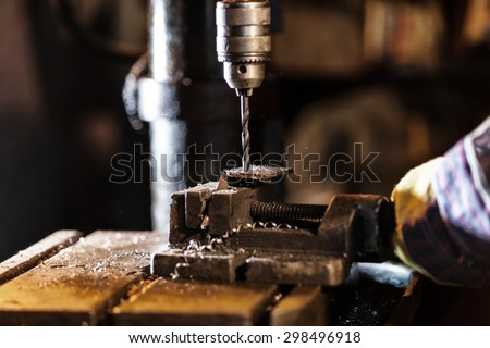 Industrial Iron drill in action in workshop interior. Closeup on the drill - stock photo