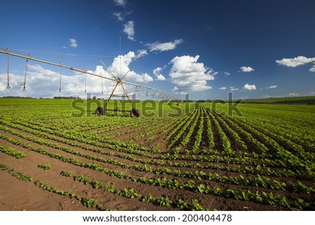 Industrial irrigation equipment on farm field under a blue sky in Brazil.