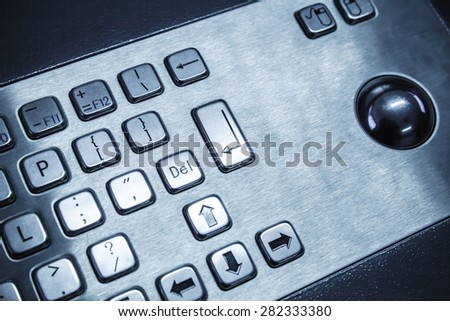 Industrial keyboard made of steel with a trackball, blue toned photo, selective focus with shallow DOF - stock photo