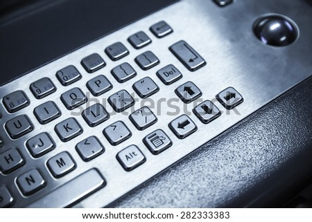 Industrial keyboard made of steel with trackball. Blue toned photo, selective focus with shallow DOF