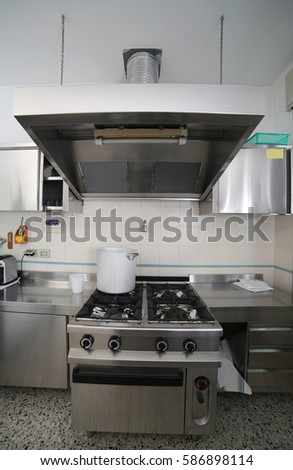 Industrial Kitchen With Steel Furniture And A Big Aluminum Pot On The Gas  Stove