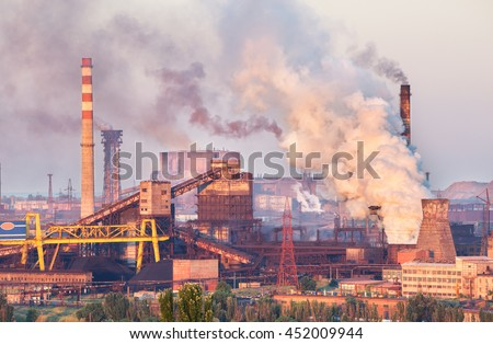 Industrial landscape in Ukraine. Steel factory at sunset. Pipes with smoke. Metallurgical plant. steelworks, iron works. Heavy industry in Europe. Air pollution from smokestacks, ecology problems.  - stock photo