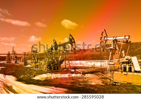 industrial landscape Oil pumps in the field on a background of sky on a sunny day in early spring instagram filter - stock photo