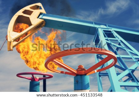 Industrial landscape. Oil valve on background of rocking and torch. - stock photo