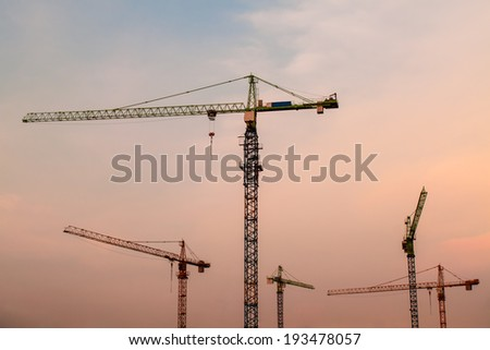 Industrial landscape with  cranes on the sunset background