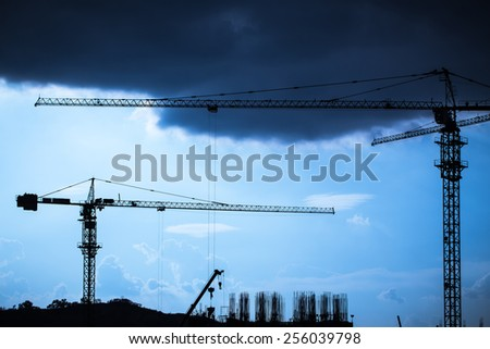 Industrial landscape with silhouettes of cranes - stock photo