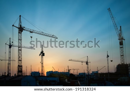 Industrial landscape with silhouettes of cranes on the sunset background - stock photo
