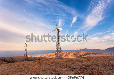Industrial landscape with wind turbine generating electricity in mountains at sunset. - stock photo