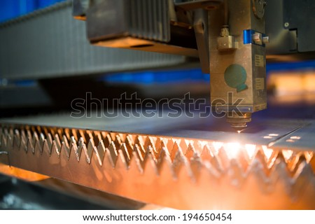 Industrial laser cutting holes in metal sheet - stock photo